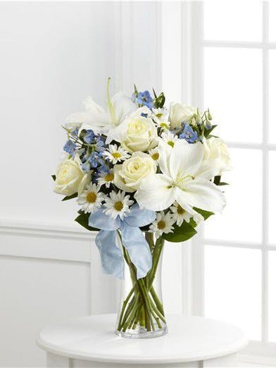 White roses, daisies, and Oriental lilies are paired with light blue delphinium and arranged in a clear glass vase