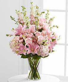 Soft pink roses, spray roses, Oriental lilies, hydrangea and larkspur are brought together in a clear glass vase