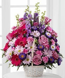 Lavender roses, fuchsia gerbera daisies, lavender daisies, purple larkspur, purple matsumoto asters, pink mini carnations and lush greens are arranged to perfection