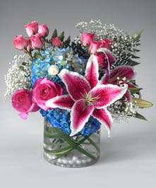 This arrangement includes hydrangea, roses, and fragrant lilies in a cylinder filled with pearls and grass.