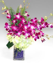 These dendrobium orchids are matched with hydrangea in a clear vase with purple gem accents.