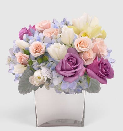Featuring roses, tulips, and orchids, this arrangement is crafted in a clear glass cube or hand-crafted purple glass cylinder.