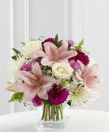 White roses, pink Asiatic lilies, carnations and a variety of lush greens are gracefully arranged in a clear glass cube