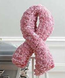 Pink carnations are designed to create the international symbol for breast cancer awareness and then displayed on an easel stand.