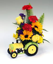 Red, yellow and blue mix with carnations roses and accent greens. this ceramic hand painted keepsake tractor is an all American gift.