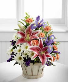 This lovely  Basket arrangement of stargazers, poms, carnations and iris will send your warmest thoughts with pink, white and blue mixed with fresh greenery